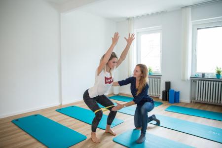 Therapeutin korrigiert Übung im Stehen