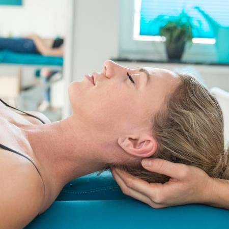Therapeuten Hände unter Patienten Kopf